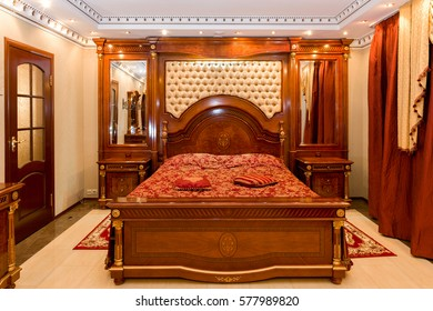 MOSCOW, RUSSIAN FEDERATION - CIRCA FEBRUARY, 2017: Hotel interior. Living room. Wooden bed with carved back. Flooring with stone tiles. White ceiling with cornice.