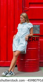 MOSCOW, RUSSIAN FEDERATION - JULY 26, 2016: Medium length dress with short sleeves. Buttons. Inner wide belt made of cloth. Milk white color, cotton. Casual fashion wear PAIGE on model.