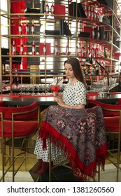 "MOSCOW, RUSSIAN FEDERATION - JUNE 10, 2018: Unique Campari Bar on 13th floor of hotel ""Pekin"" in Moscow city (Russia). Beaituful girl with cocktail and Pavlovo Posad shawl"