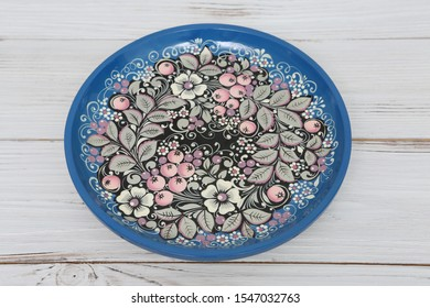 MOSCOW, RUSSIAN FEDERATION – OCTOBER 30, 2019: Ancient russian traditional national handcraft: plate with north khokhloma painting. Vintage wooden ware. Best souvenir from Russia. Russian folk style
