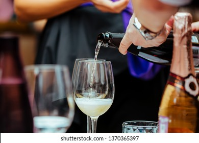 Moscow, Russian Federation-March 30, 2019: wine tasting: Champagne is poured into a glass standing on the table. Close up.