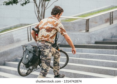 MOSCOW, RUSSIN FEDERATION - JULY 28, 2017: Side view of a camouflaged male cyclist with bicycle under his arm walking up steps