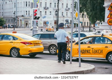 MOSCOW, RUSSIN FEDERATION - JULY 28, 2017: The inspector policeman stopped Yandex taxi driver, in Moscow in Russia during summer season - Image
