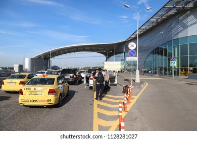 MOSCOW, RUUSIA - JUNE 24, 2018: Taxi cars and people outside the terminal building at Sheremetyevo airport in Moscow, Russia