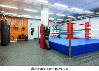 MOSCOW - SEP 17, 2013: Empty hall for boxing in a gym. Fitness club with equipment. Panorama of a clean modern gym with a blue and red boxing ring.