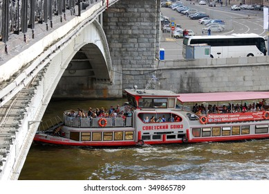 MOSCOW - SEPTEMBER 06, 2014: Cruise ship Soviet Union sails on the Moskva river under the Big Stone Bridge in Moscow city historical center, popular landmark.