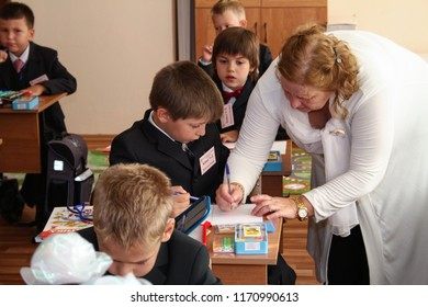 Moscow - September 1, 2011: The teacher teaches the first class student to write at the day of knowledge. Public-event.