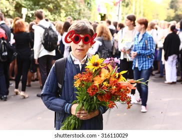 """MOSCOW, SEPTEMBER 1, 2015: Unidentified boy in funny """"cool"""" glasses with flowers celebrate first school day at September 1, Moscow."""