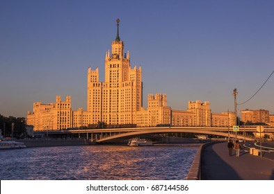 Moscow urban landscape with high-rise building, Moscow River, Bolshoy Ustinsky Bridge and urban transport as boats, trams at summer sunset. Russia.