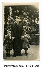 """MOSCOW, USSR - CIRCA 1950s : An antique photo shows young father and his two daughters twins. """"Soviet people"""" series."""