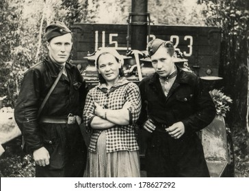 """MOSCOW, USSR - CIRCA 1960s : An antique photo shows Two soldiers of the Red Army and their girlfriend. """"Soviet people"""" series"""
