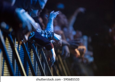 MOSCOW-1 FEBRUARY,2017:Front row of concert audience in nightclub.Music festival crowd behind metal security fence.Hands of young hip hop fans on entertainment event in the club