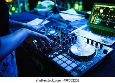MOSCOW-1 MARCH,2016:Dj girl plays music on stage in nightclub.Hip hop party dj girl mix tracks.Female disc jockey performs live set on scene in bright blue stage lights.Digital dj turn table player