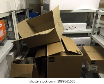 Moscow,1 May 2018:Poorly organized warehouse with a lot of messy stocks and boxes. Abandoned carton boxes on steel racks with metal beam construction in storage. unwanted stuff in box.