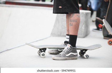 MOSCOW-1 MAY,2016:Skateboarding contest in skate park Plaza.Young skateboarder ride in outdoor concrete skatepark.Tattooed feet of cool skate boarder guy.Ready to roll on skate board