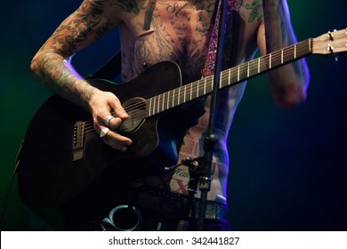 MOSCOW-10 NOVEMBER,2015:Professional guitarist with tattoos plays acoustic guitar on stage in music hall.Rock music concert stage.Musician plays guitars on scene.Concert of singer MGK playing guitars