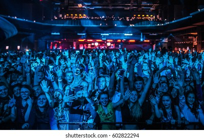 MOSCOW-11 OCTOBER,2015:Group of happy young people on rap concert in night club .Crowded dancefloor with excited music fans.Musical festival audience on entertainment event in bright blue stage light
