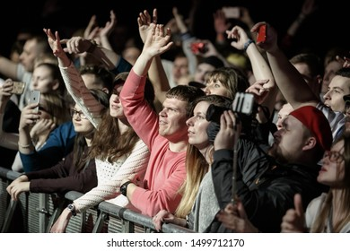 MOSCOW-13 APRIL,2017: Young people raise hands to favorite rap singer Ligalize on concert in night club.Music fans enjoying the party in front row behind security fence on dance floor near stage