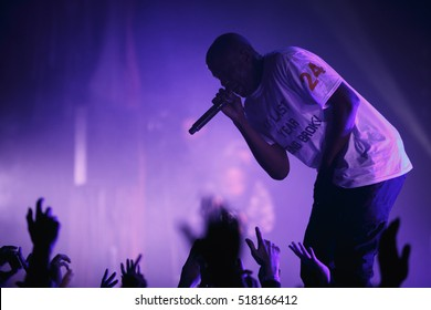 MOSCOW-15 NOVEMBER,2016:Famous rap band Asap Mob performing live hip hop music show on nightclub stage.Black rapper singer with microphone on scene.Concert in crowded nightclub.Music fans put hands up