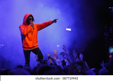 MOSCOW-16 FEBRUARY,2017:Cool rap singer Jazz Cartier performing on stage in night club.Popular rapper sings in microphone on scene.Music festival event in nightclub.Hip hop concert background