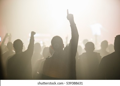 MOSCOW-18 DECEMBER,2016:Dj concert in night club.Music fans on crowded club dancefloor wave hands in air.Cool nightclub party,people put hands up,enjoy music festival.Yellow club stage bright lighting