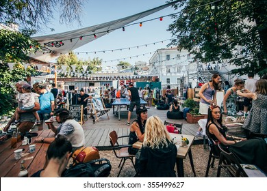 MOSCOW-2 AUGUST,2015:Hipster event on back yard.Outdoor summer fastfood court.Street food festival.Group of young people eat barbecue together outside in street cafe.Backyard bbq party.