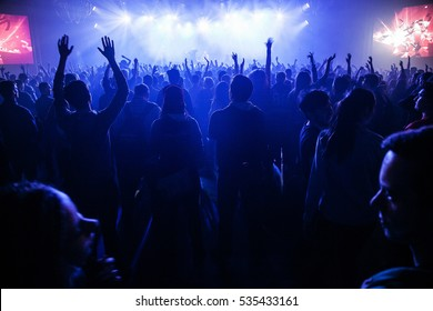 MOSCOW-2 FEBRUARY,2015:Concert crowd party in night club on edm dj concert.Bright blue concerts lights in big nightclub.Group of young people partying.Silhouette of happy music fans