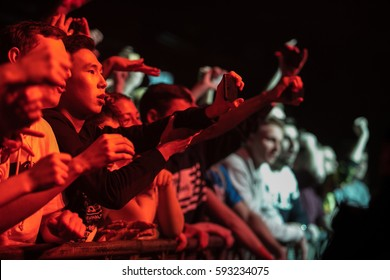 MOSCOW-2 FEBRUARY,2017:Excited young Asian music fan film rap music concert in night club with smartphone.Young fans taking pictures of singer on stage.Bright concert lighting on dance floor