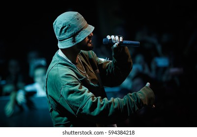 MOSCOW-2 FEBRUARY,2017:Portrait of rap singer Miyagi singin in radio microphone on stage in night club.Bright concert green lights background.Rapper with mic in hand.Famous hip hop performer sings