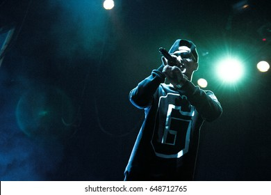 MOSCOW-2 OCTOBER,2014:Rapper with mic in hand.Rap music concert in the club.Cool young singer with microphone on stage in bright green concert lights.Popular entertainment event for youth