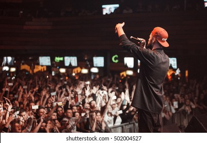 MOSCOW-2 OCTOBER,2016:Cool young rap singer Miyagi sings in microphone on stage.live music concert in night club.Big crowd on music festival.View from stage on hip hop event
