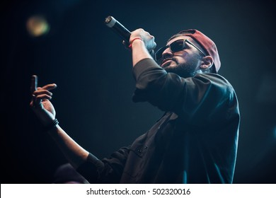 MOSCOW-20 OCTOBER,2016:Cool rap singer Miyagi sings on night club stage.Hip hop music performer singing in microphone on scene.Rapper in bright concert lighting