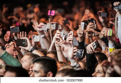 MOSCOW-20 OCTOBER,2016:Crowded dance floor in nightclub.Big live musical show in the club.Music fans with smartphone camera film concerts main event.Group of young people with phones on festival