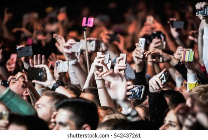 MOSCOW-20 OCTOBER,2016:Crowded dancefloor in nightclub.Hands of fans with smart phone mobile camera film dj concert.Music show in night club.Music festival crowd filming show with smartphones