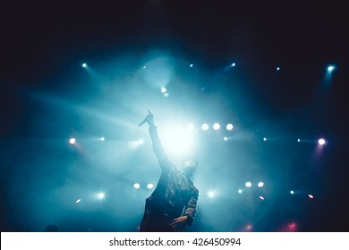 MOSCOW-27APRIL,2016: Concert of hip hop band Krec on club stage in bright lights.Famous rap singer sing on scene.Cool rap singer put hand with microphone up in blue light