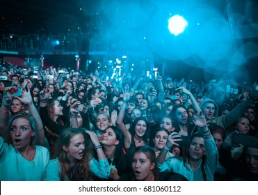 MOSCOW-3 MARCH,2016:Night club concert crowd partying on concert in music hall.EDM festival audience party hard to the famous dj set on stage.Bright blue lights background.Music fans wave hands