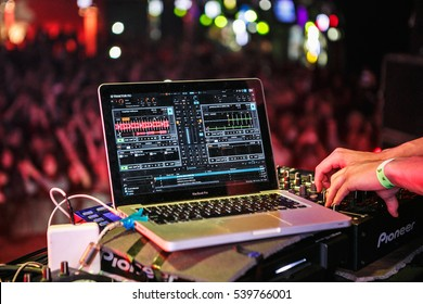 MOSCOW-3 NOVEMBER,2016:Club dj mix digital music tracks in nightclub on Native Instruments Traktor DJ Scratch Pro mixing software installed on Apple MacBook Pro.Disc jockey plays concert on stage