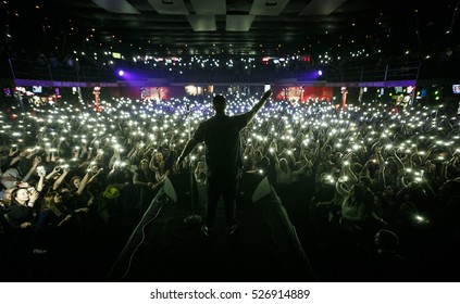 MOSCOW-3 NOVEMBER,2016:Popular rap singer on stage.Pop music concert in nightclub.Musician on scene,view from stage on festival audience in music hall.Fans put mobile phone lights on to favorite song
