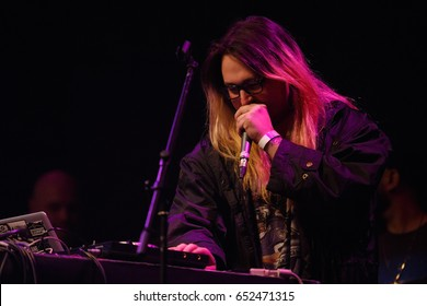 MOSCOW-30 MARCH,2017: Famous club dj talks in microphone on hip hop concert of Lil Peep.Cool young man with long hair singing in mic on stage.Dj talk on stage.Popular edm disc jockey play set on scene