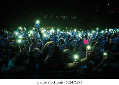 MOSCOW-30 MARCH,2017:Concert crowd party.Big group of young music fans partying to favorite dj playing on stage.Edm music festival audience raving at security fencing.Mobile phone lights up on rave