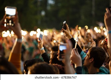 MOSCOW-4 JULY,2017:Big concert crowd on outdoor summer festival.Music gig fans put hands with phone light up to favorite song on stage.Group of young people partying on edm entertainment event outside