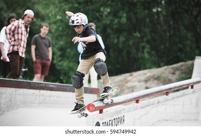 MOSCOW-5 MAY,2016:Young teenager skater boy grinds on rail in skatepark.Skate contest in summer.Sporty teen boy in helmet,knee pads grinds rail in skate park outdoor.Extreme skateboarding competition