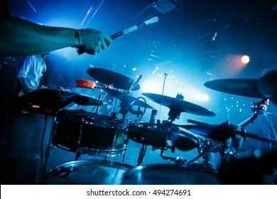 MOSCOW-5 OCTOBER,2016: Drummer boy play live set on stage in bright blue lighting.Drums player playing on drum set.Rock band play live music concert in club.Musician play with drum sticks on drumset