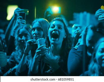 MOSCOW-5 SEPTEMBER,2016:Excited young girl screams on concert.Happy young females have fun in club.Concert crowd screaming.Festival audience on dance floor.Crazy music fans in blue lights