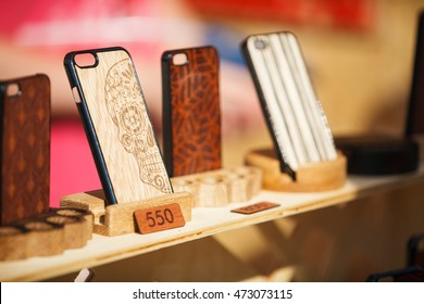 MOSCOW-6 AUGUST, 2016: Handmade wooden iPhone cases on sale in mobile phone accessories shop.Hand crafted wood case for smartphones.Art work on wooden mobile phone case covers