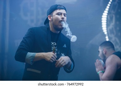 MOSCOW-6 DECEMBER,2016:Vaper guy blows white smoke circles in the air with mech mod vaporizer device.Vaper Expo event.Vape cloud trick show on stage.Young vaper man vapes circles with ejuice smoke