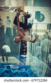 MOSCOW-6 SEPTEMBER,2015:Young skateboarder in helmet jump with backflip trick on big indoor ramp in skatepark during skating contest.Teen skater boy makes back flips on skateboard in skating park