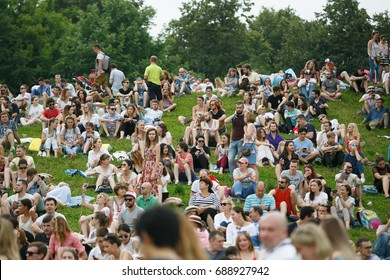 MOSCOW-9JULY,2017:Music fans enjoy big outdoor entertainment event.Open air festival Picnic.Big group of young people sit on grass waiting for music show to begin.Summer gig crowd partying on holiday