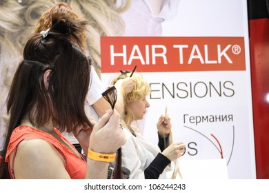MOSCOW-APRIL 19: Hairdresser increases a client hair at the international exhibition of professional cosmetics and beauty salon equipment INTERCHARM on April 19, 2012 in Moscow