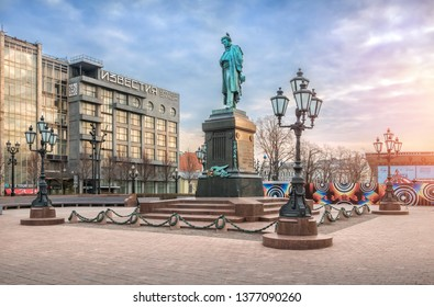 Moscow/Russia - 04/21/2019. A monument to Pushkin on Pushkin Square in Moscow next to the building of Izvestia among the lanterns on a cloudy spring morning